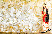 Beautiful Indian female in colorful sari full length walking in front of marble wall