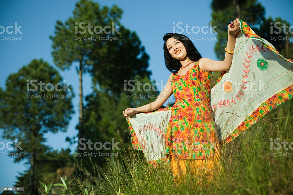 Beautiful Indian girl flying dupatta like her wings in nature. stock photo