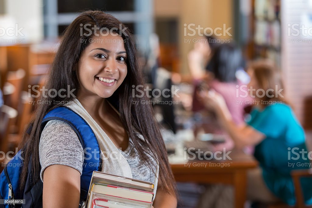 Beautiful Indian high school girl smiling in library before studying stock photo