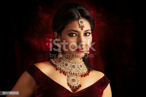 Beautiful Indian traditional bride portrait on dark background.