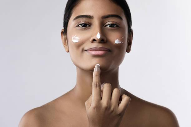 Beautiful Indian woman applying moisturizing cream on her face stock photo