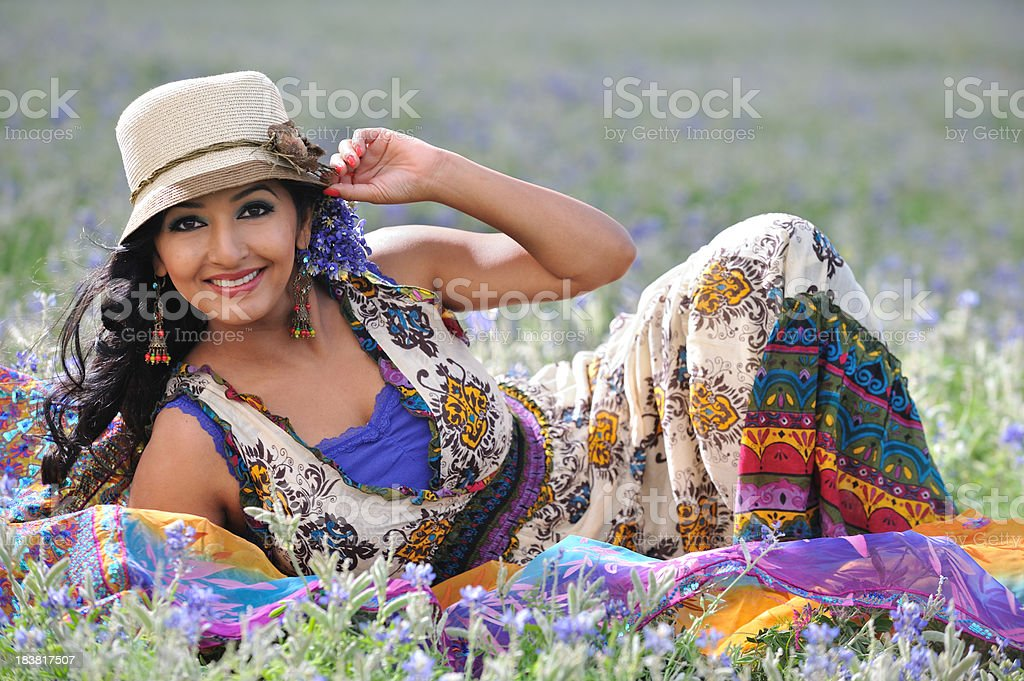 Beautiful Indian woman in a field of wildflowers stock photo