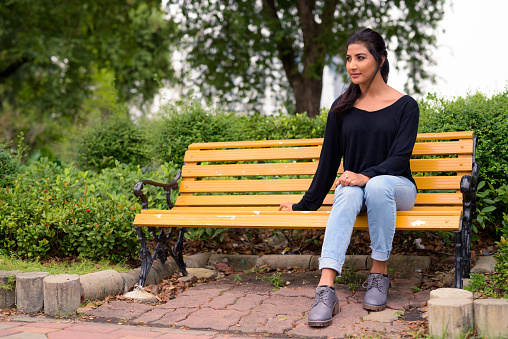 Beautiful Indian Woman Sitting At Park Bench Stock Photo - Download Image  Now - iStock