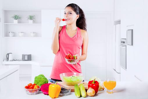 istock Beautiful Indian Woman tasting strawberry 916874276