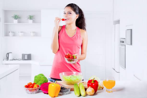 Beautiful Indian Woman tasting strawberry