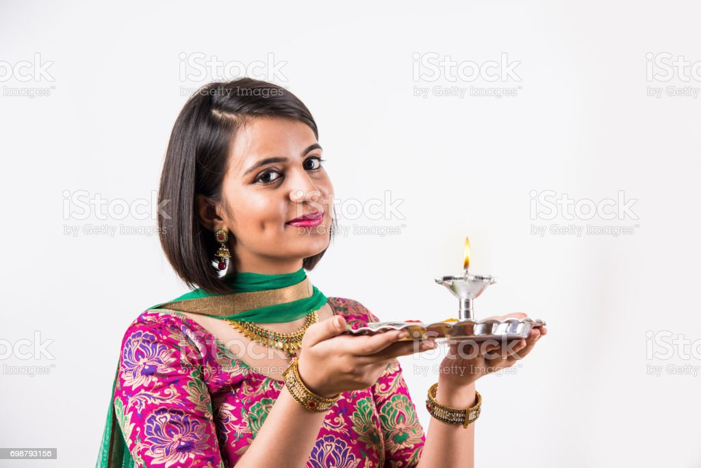 beautiful Indian young girl performing puja, indian girl with pooja thali or puja thali, portrait of a beautiful young lady with pooja thali, isolated overwhite background stock photo