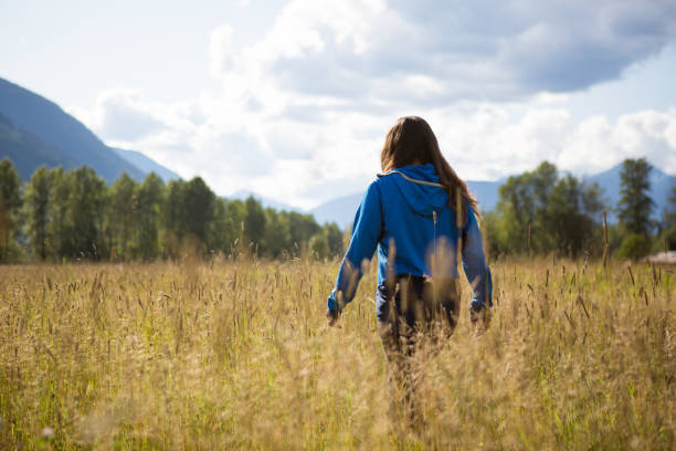 Beautiful indigenous Canadian woman wondering through a field stock photo