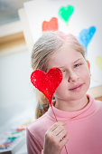 istock Beautiful innocent girl with red heart 918057580