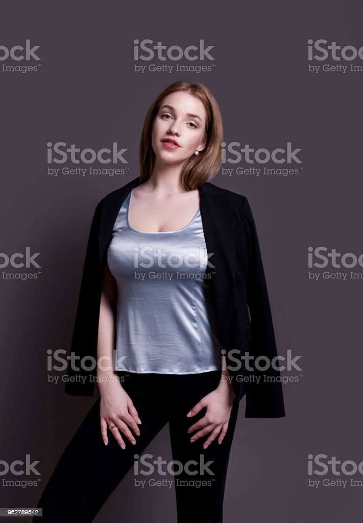 Beautiful intelligent young woman looking confident and happy wearing smart casual clothes Studio portrait on gray background - Foto stock royalty-free di Abbigliamento