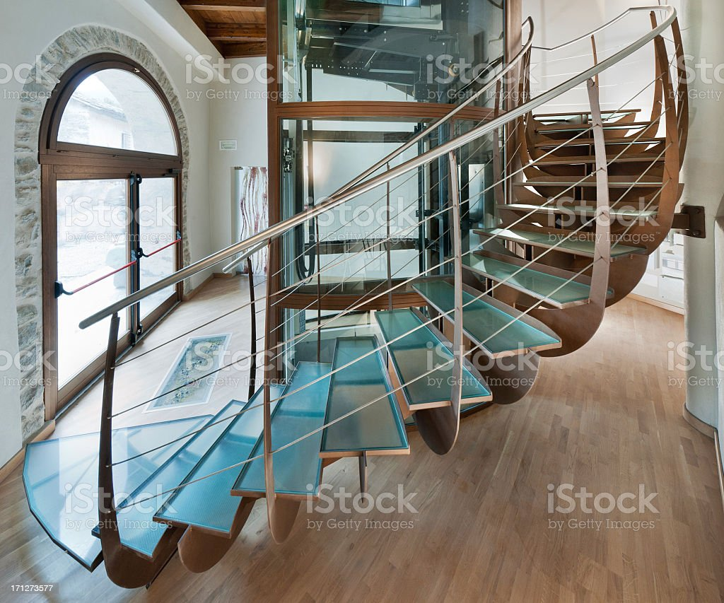 Beautiful interior iron and glass spiral staircase surrounding a lift royalty-free stock photo