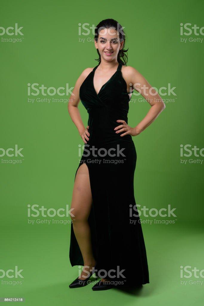 b89f874828e Beautiful Iranian woman wearing black sleeveless dress against green  background royalty-free stock photo