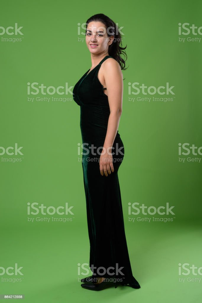Beautiful Iranian woman wearing black sleeveless dress against green background royalty-free stock photo