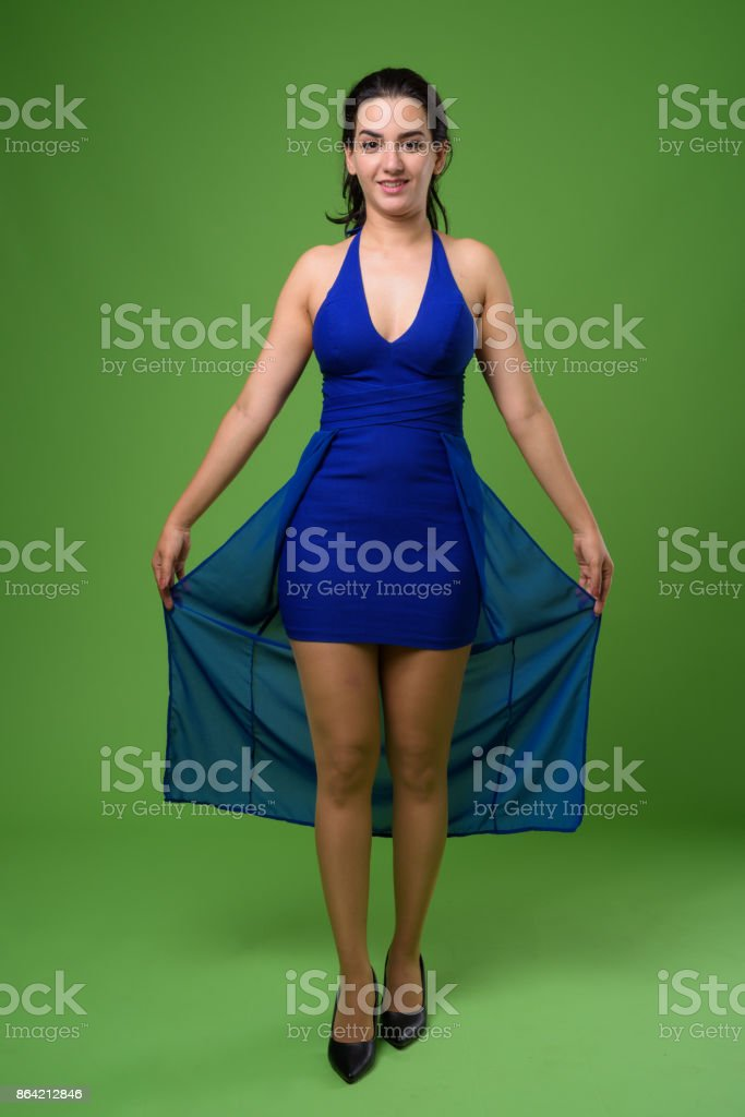Beautiful Iranian woman wearing blue sleeveless dress against green background royalty-free stock photo
