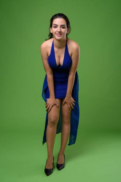 Beautiful Iranian woman wearing blue sleeveless dress against green background stock photo