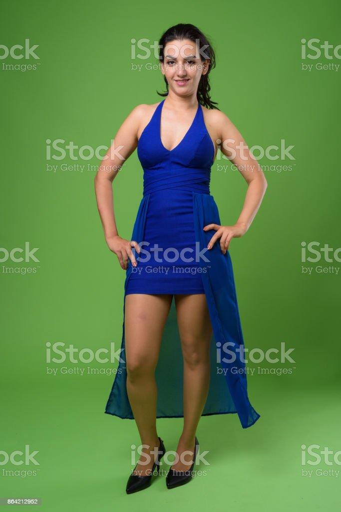 Beautiful Iranian woman wearing blue sleeveless dress against green background royalty-free stock photo