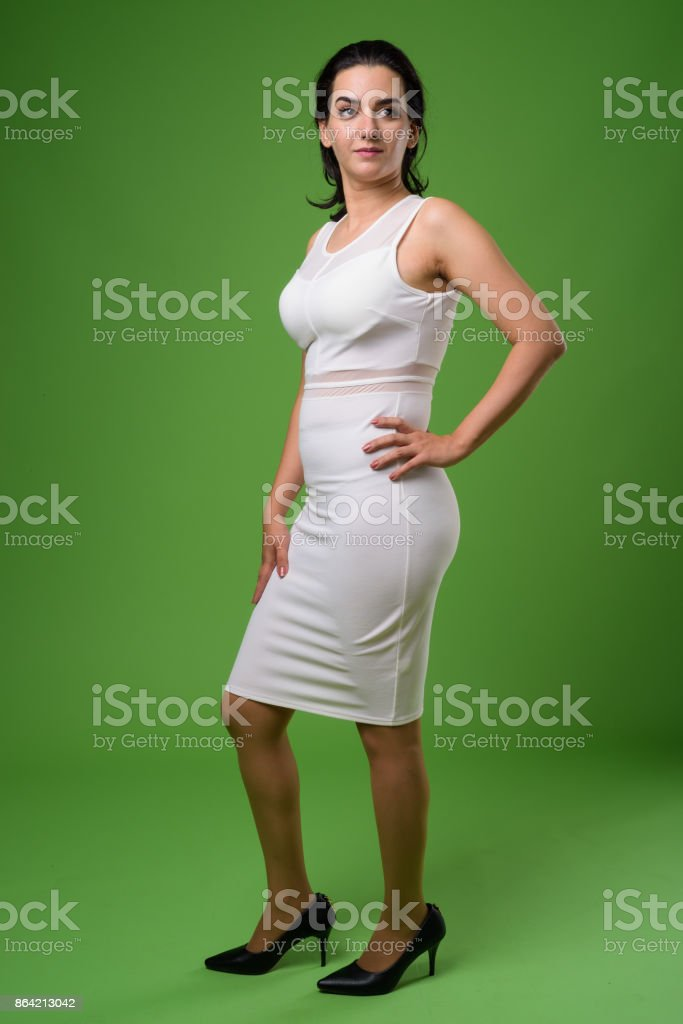 Beautiful Iranian woman wearing white sleeveless dress against green background royalty-free stock photo