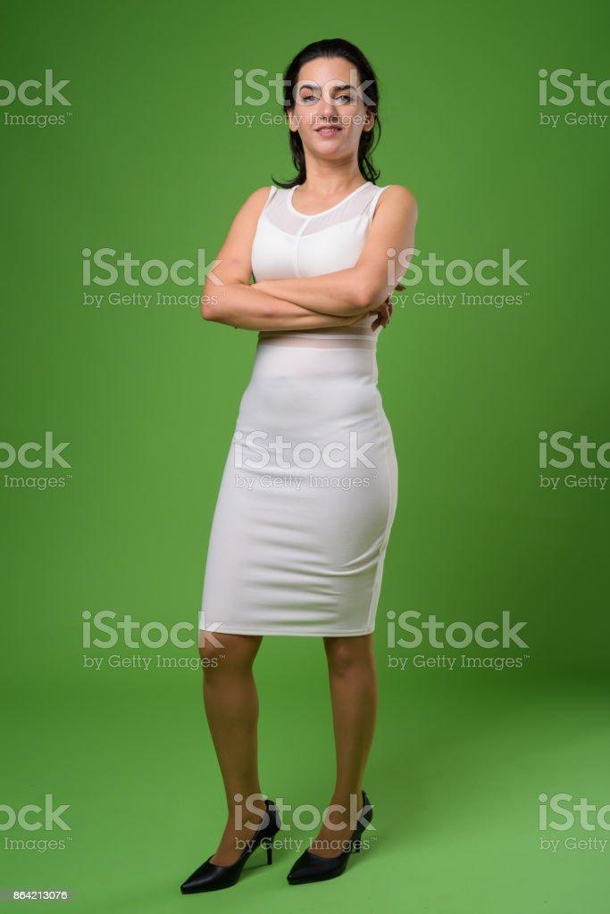 Beautiful Iranian woman wearing white sleeveless dress against green background royalty-free stock photo