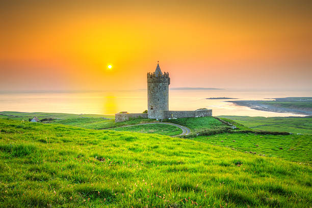 beautiful irish castle near atlantic ocean at sunset, co. clare - the burren stock pictures, royalty-free photos & images