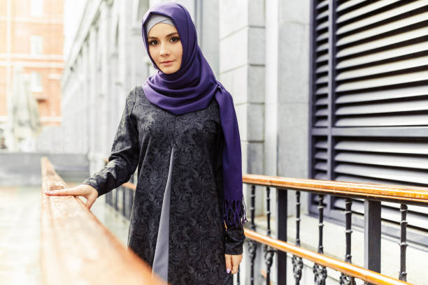 Beautiful Islamic woman in traditional oriental clothes standing on a city street stock photo