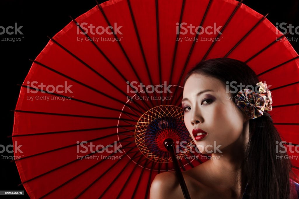 Beautiful Japanese geisha with a red umbrella royalty-free stock photo