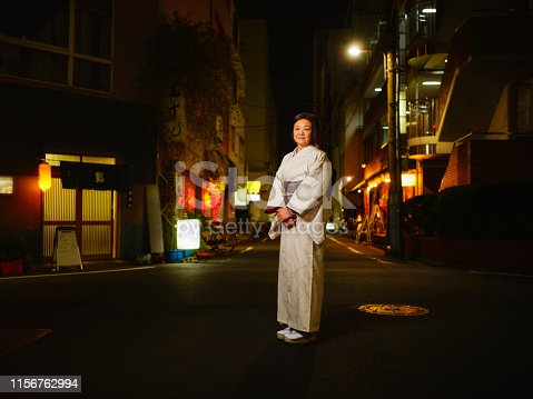 A beautiful senior aged Japanese woman standing in a small city area at night while wearing a traditional kimono.
