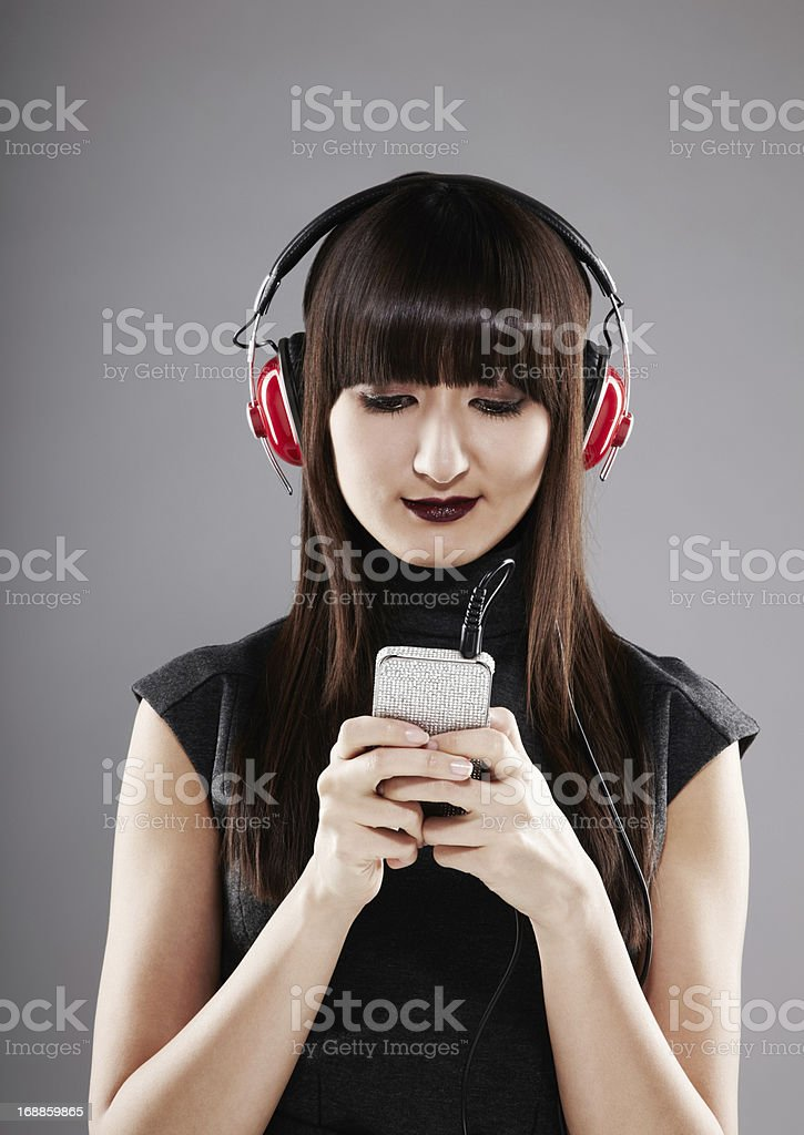 Beautiful Japanese woman listening to music on red headphones royalty-free stock photo