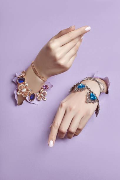 vackra smycken på händerna på kvinnor, händer med arm band och halsband sticker ut från trasiga violett lila papper bakgrund. reklam smycken och smycken, kopierings utrymme - hand gold jewels bildbanksfoton och bilder