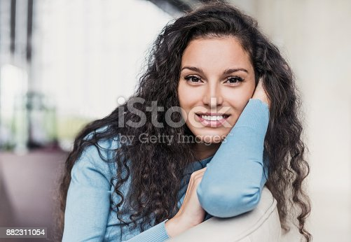 istock Beautiful joyful woman relaxing on sofa at home 882311054