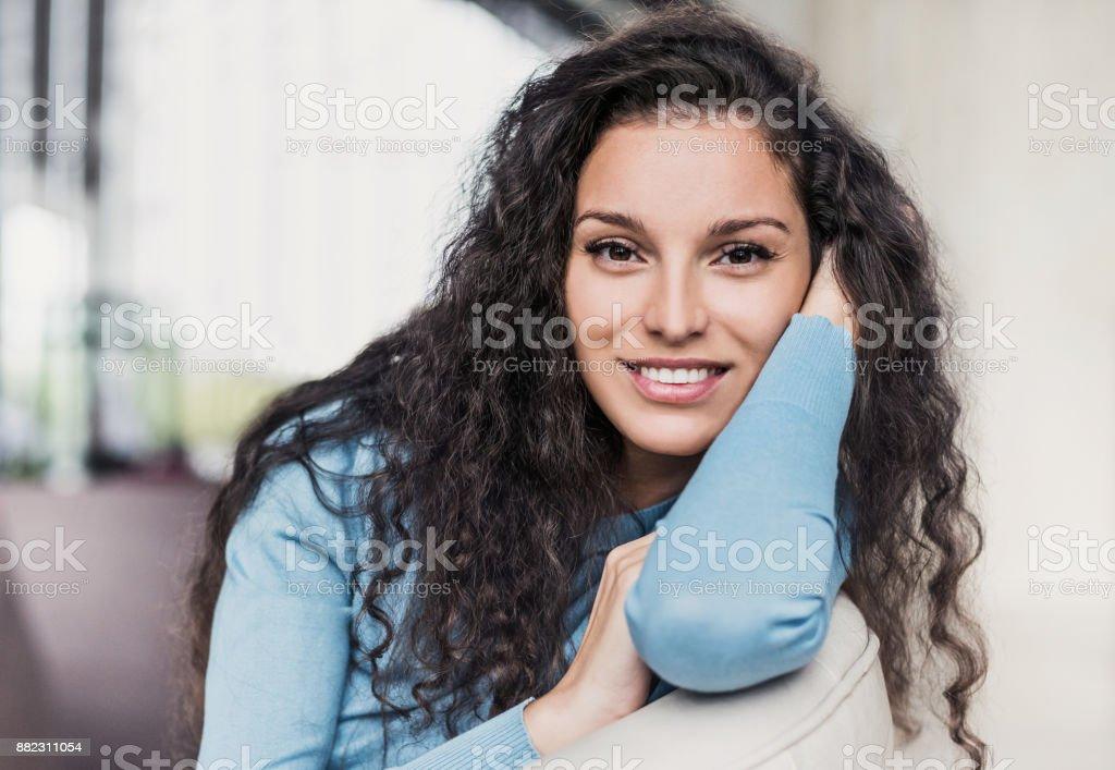 Beautiful joyful woman relaxing on sofa at home stock photo