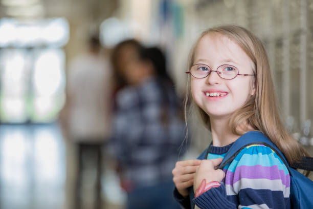 Beautiful junior high school student with Down Syndrome smiles on her way to class Beautiful junior high school student with Down Syndrome smiles on her way to class cute middle school girls stock pictures, royalty-free photos & images