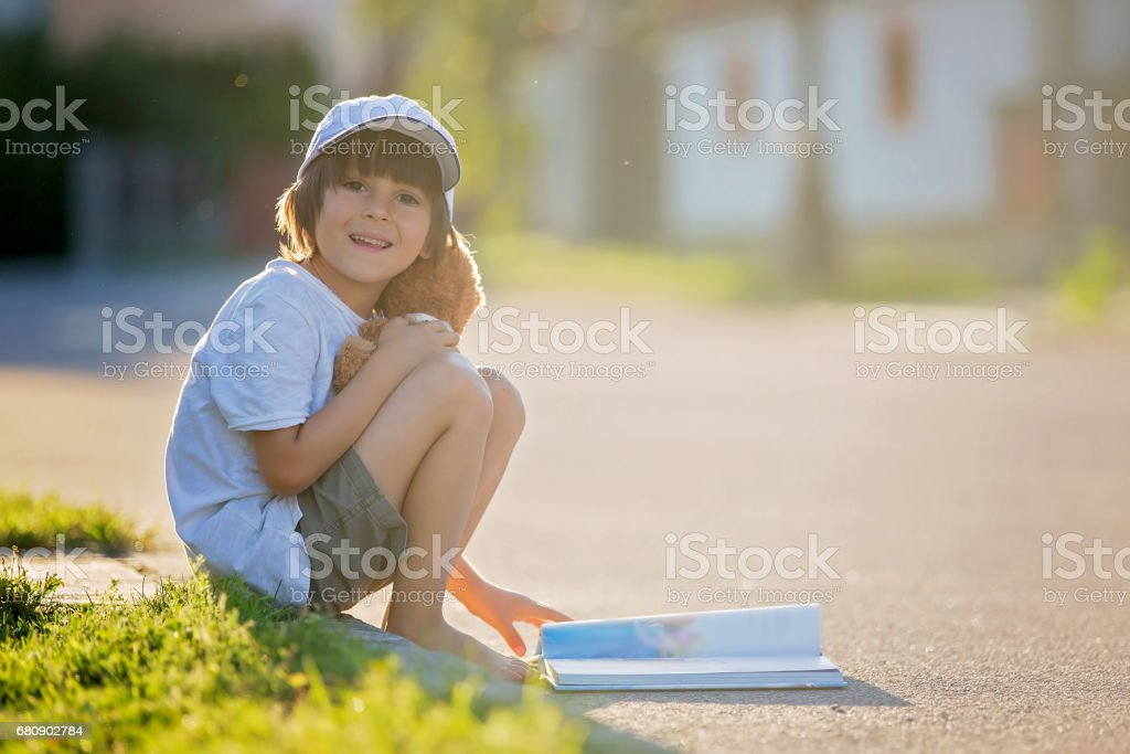 Beautiful kid boy, reading a book on the street, sitting down with teddy bear, gorgeous sunset light royalty-free stock photo