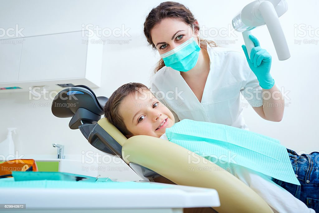 Beautiful kid boy smiling in dentist's chair the office stock photo