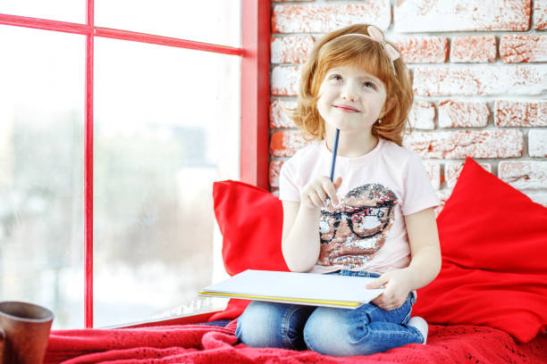 Beautiful kid fantasizes and paints on the windowsill. The conce Beautiful kid fantasizes and paints on the windowsill. The concept is childhood, learning, drawing, hobbies, education, talent. deem stock pictures, royalty-free photos & images