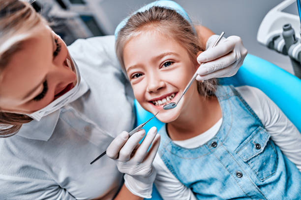 Beautiful kid girl smiling in dentist's chair the office treats teeth. Doctor mask and child looks at camera. stock photo