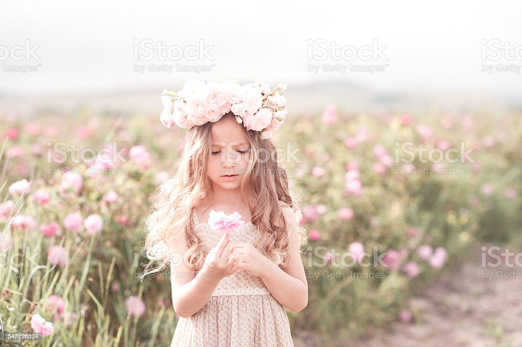Beautiful kid girl with flower outdoors stock photo