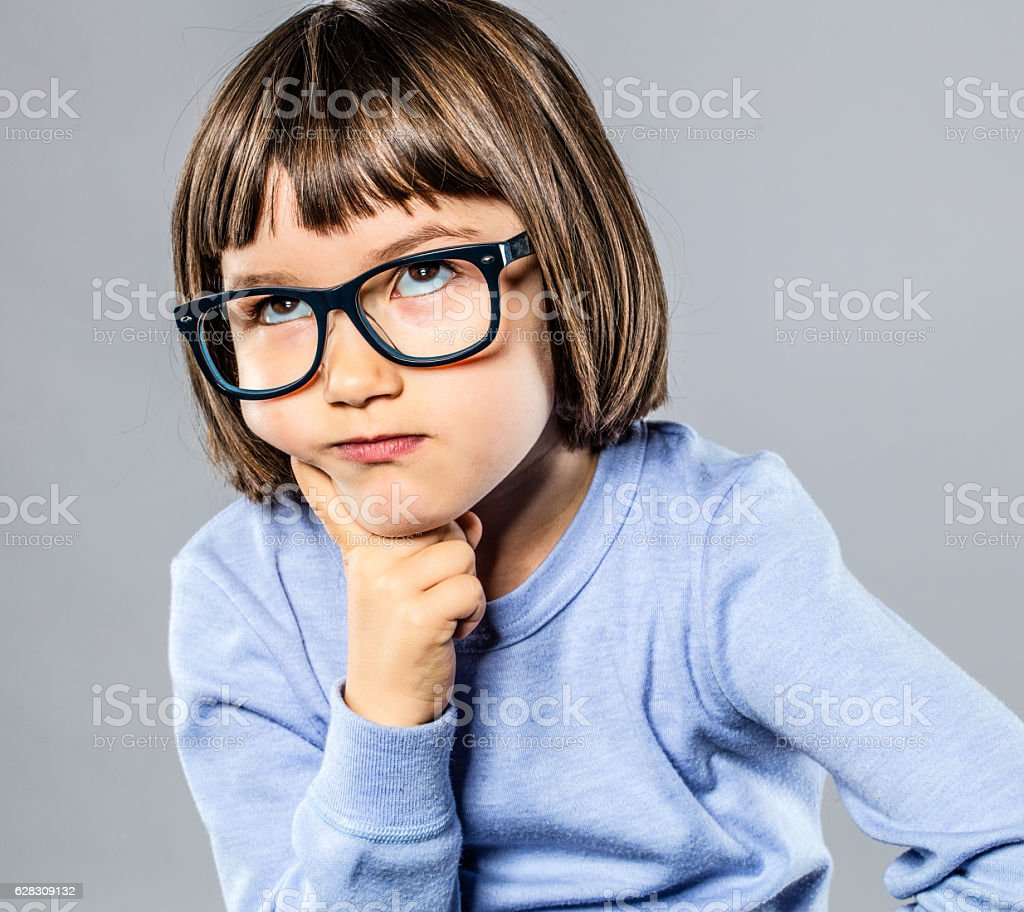 beautiful kid playing Thinker with serious eyeglasses for intelligent solution stock photo