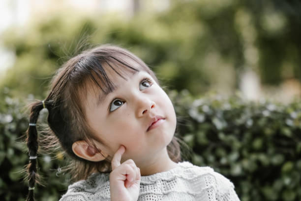 Beautiful kid playing Thinker with serious Portrait, pigtails, thinking, planning, positive emotion, Ideas, Inspiration, creativity, studying, learning, garden, nature, Asian and Indian Ethnicities baby girls stock pictures, royalty-free photos & images