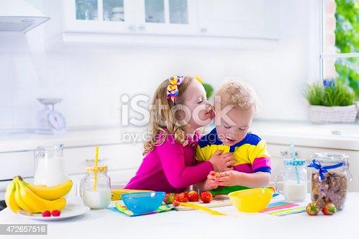 istock Beautiful kids preparing breakfast in a white kitchen 472657516