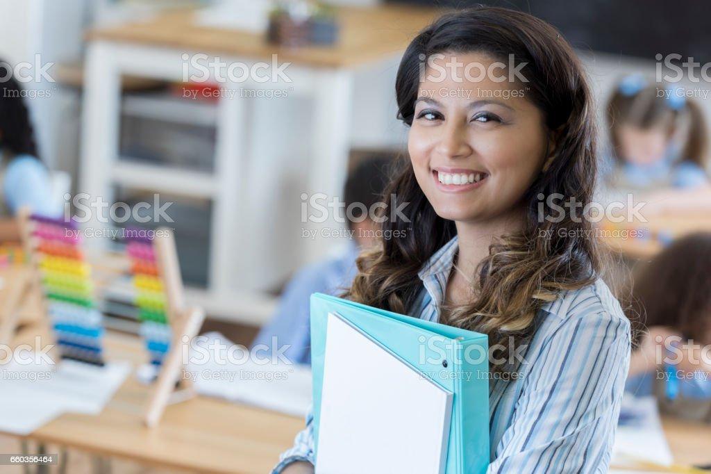 Beautiful kindergarten teacher in the classroom stock photo