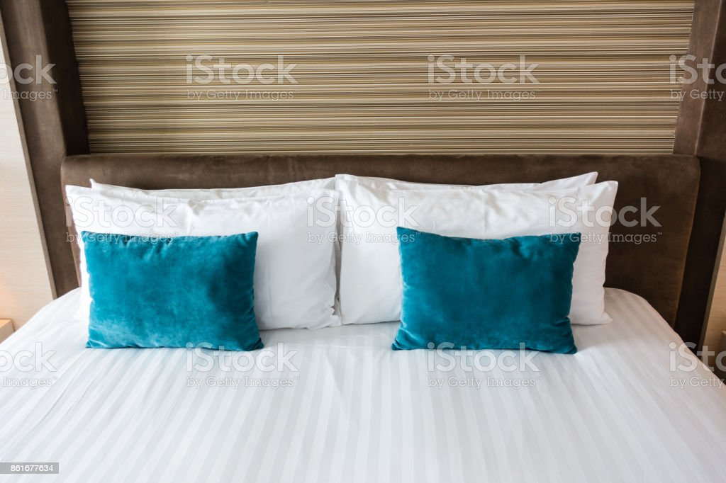 Beautiful king size bed with blue and white pillows stock photo