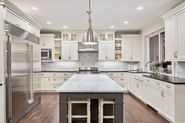 schöne küche in luxus zu hause mit insel und edelstahl - landküche stock-fotos und bilder