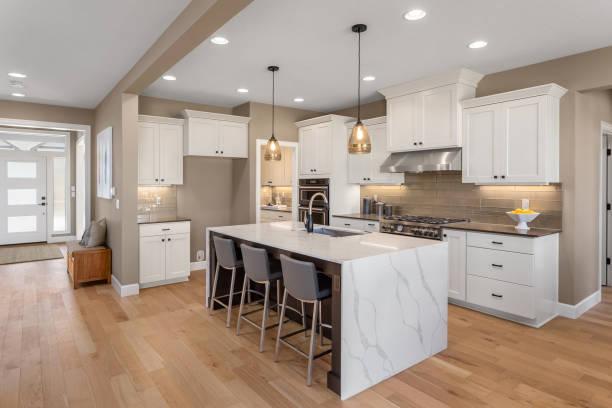 piękna kuchnia w nowym domu z wyspą, lampami wiszącymi i drewnianymi podłogami. - kuchnia zdjęcia i obrazy z banku zdjęć