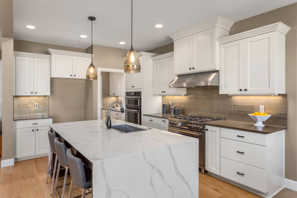 beautiful kitchen in new home with island, pendant lights, and hardwood floors. stock photo