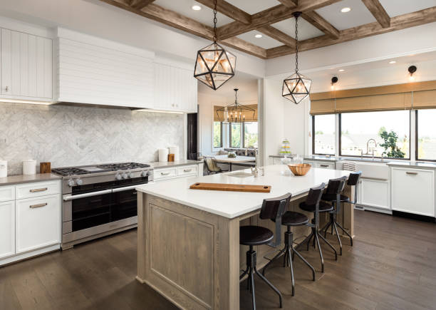 beautiful kitchen in new luxury home with island and pendant light fixtures - kitchen imagens e fotografias de stock