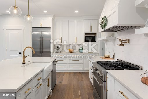 istock beautiful kitchen in new luxury home with island, pendant lights, and hardwood floors 1054756110
