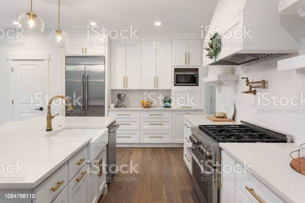 Beautiful kitchen in new luxury home with island pendant lights and picture id1054756110?b=1&k=6&m=1054756110&s=612x612&h=wxdidwigzvbivdyl3clfhamxxglccabcqsuygb2adqu=