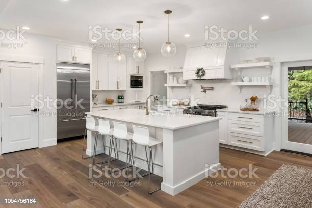 Beautiful kitchen in new luxury home with island pendant lights and picture id1054756164?b=1&k=6&m=1054756164&s=612x612&h=wye 34prkwnjmjg68xwnbjy7 p65vf61mllfg5q  ng=