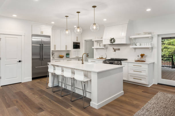 beautiful kitchen in new luxury home with island, pendant lights, and hardwood floors stock photo