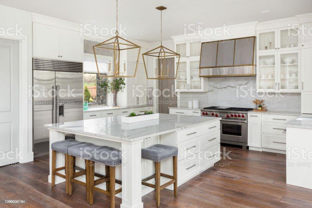 vackra kök i nya lyxhus med ön, hänge belysning och trägolv - Royaltyfri Amulett Bildbanksbilder
