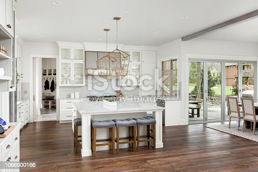 istock beautiful kitchen in new luxury home with island, pendant lights, and hardwood floors 1066000166